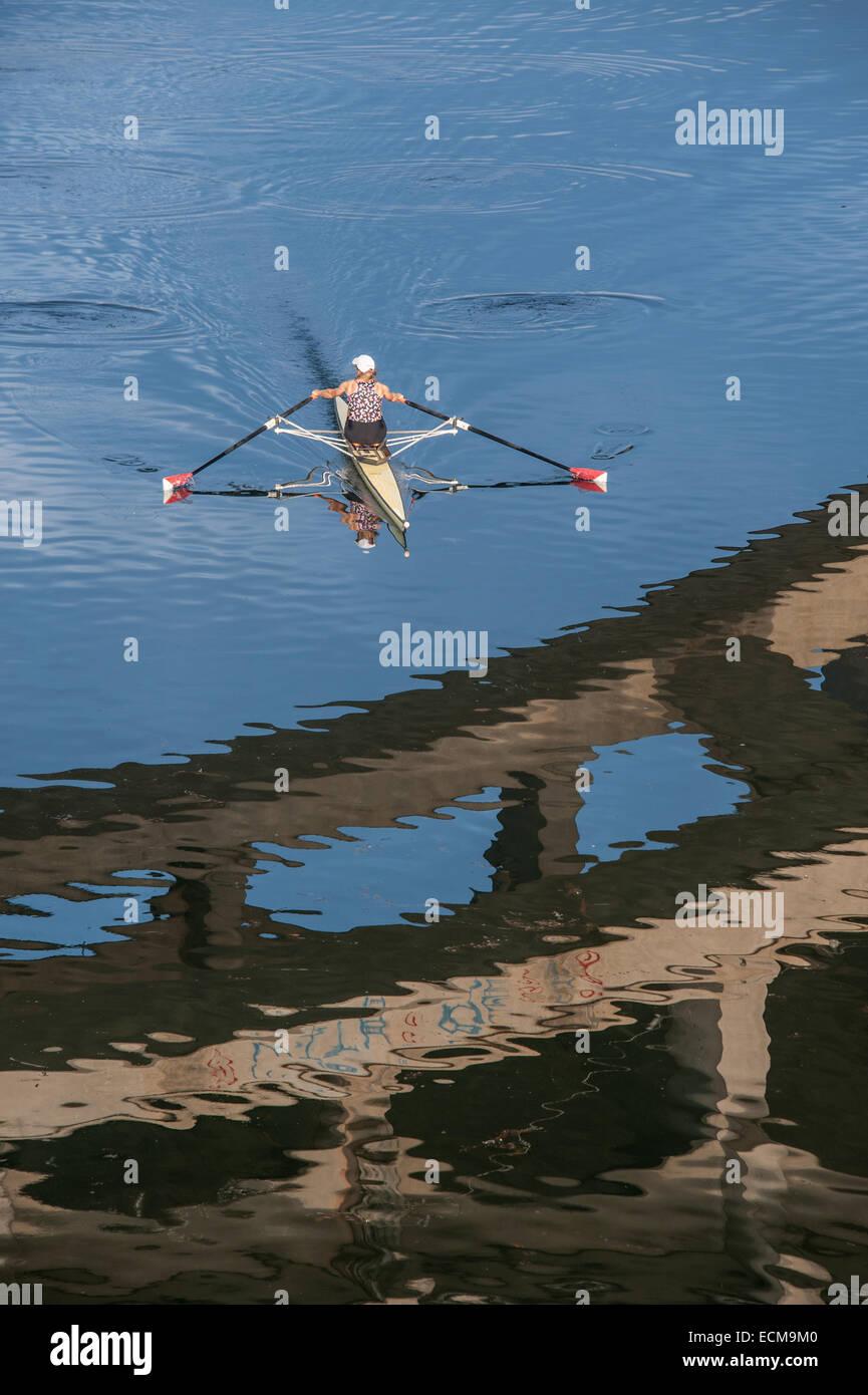 Un vogatore sul Lago Lady Bird di Austin in Texas visto con una campata del ponte di Lamar visibile riflessa nell'acqua. Immagini Stock