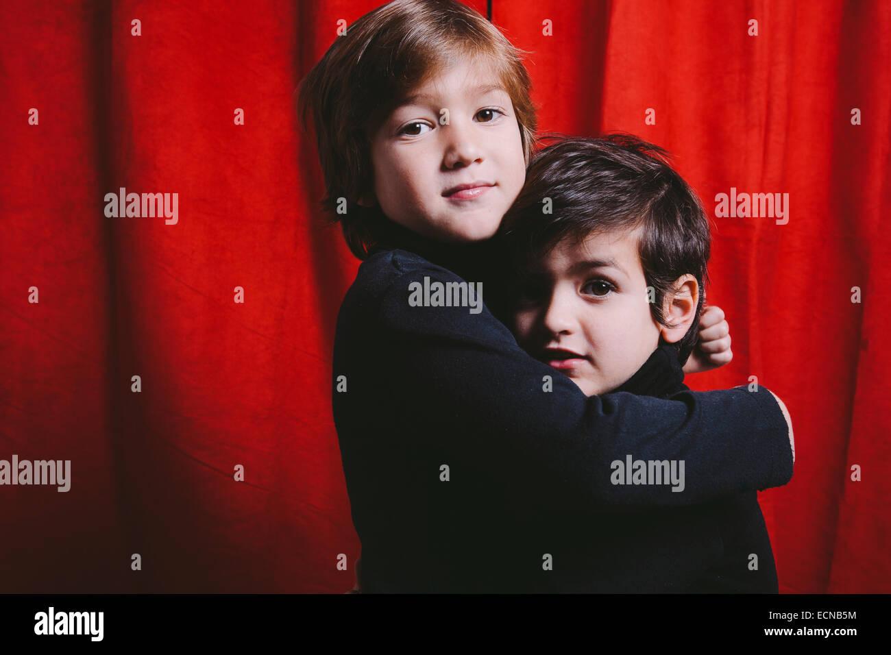Due ragazzi che indossa abiti neri su un abbraccio Immagini Stock