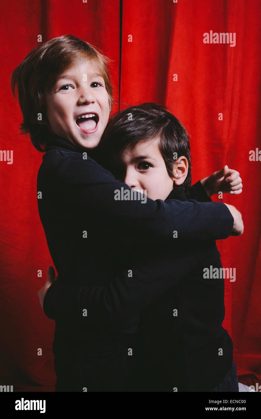 Ritratto in studio di due ragazzi che indossa abiti neri su un abbraccio Immagini Stock
