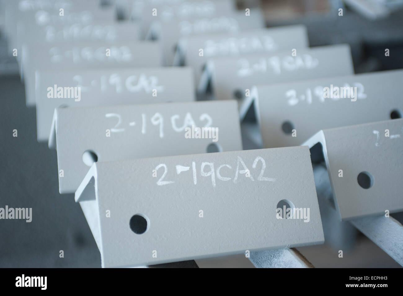 Angoli di clip in negozio di fabbricazione di metalli contrassegnato con il numero di parte. Immagini Stock