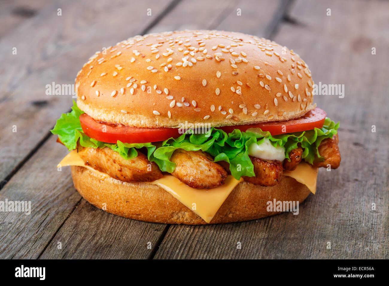 Hamburger di pollo e formaggio su una superficie in legno Foto Stock