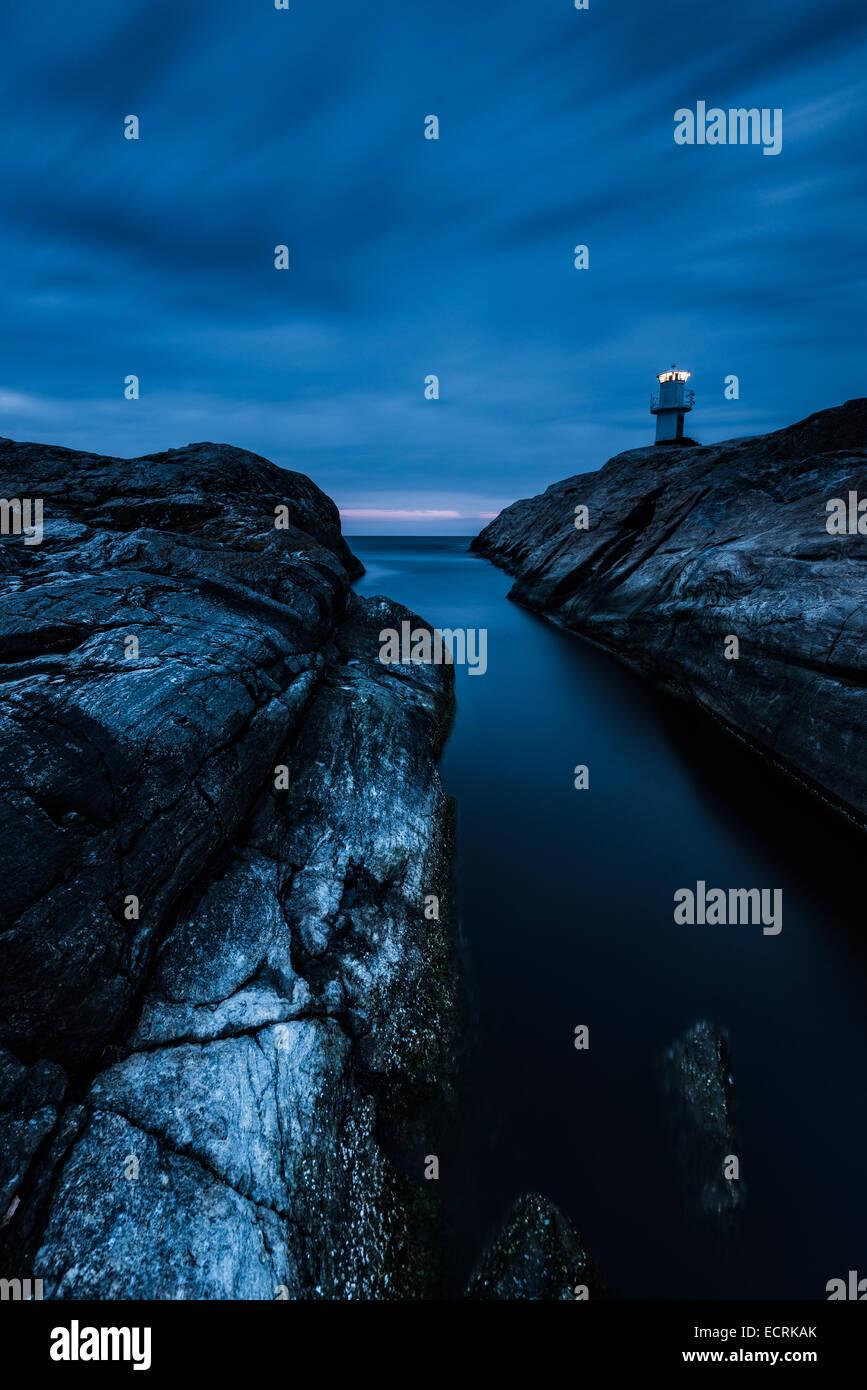 Faro e una spiaggia rocciosa di notte Immagini Stock