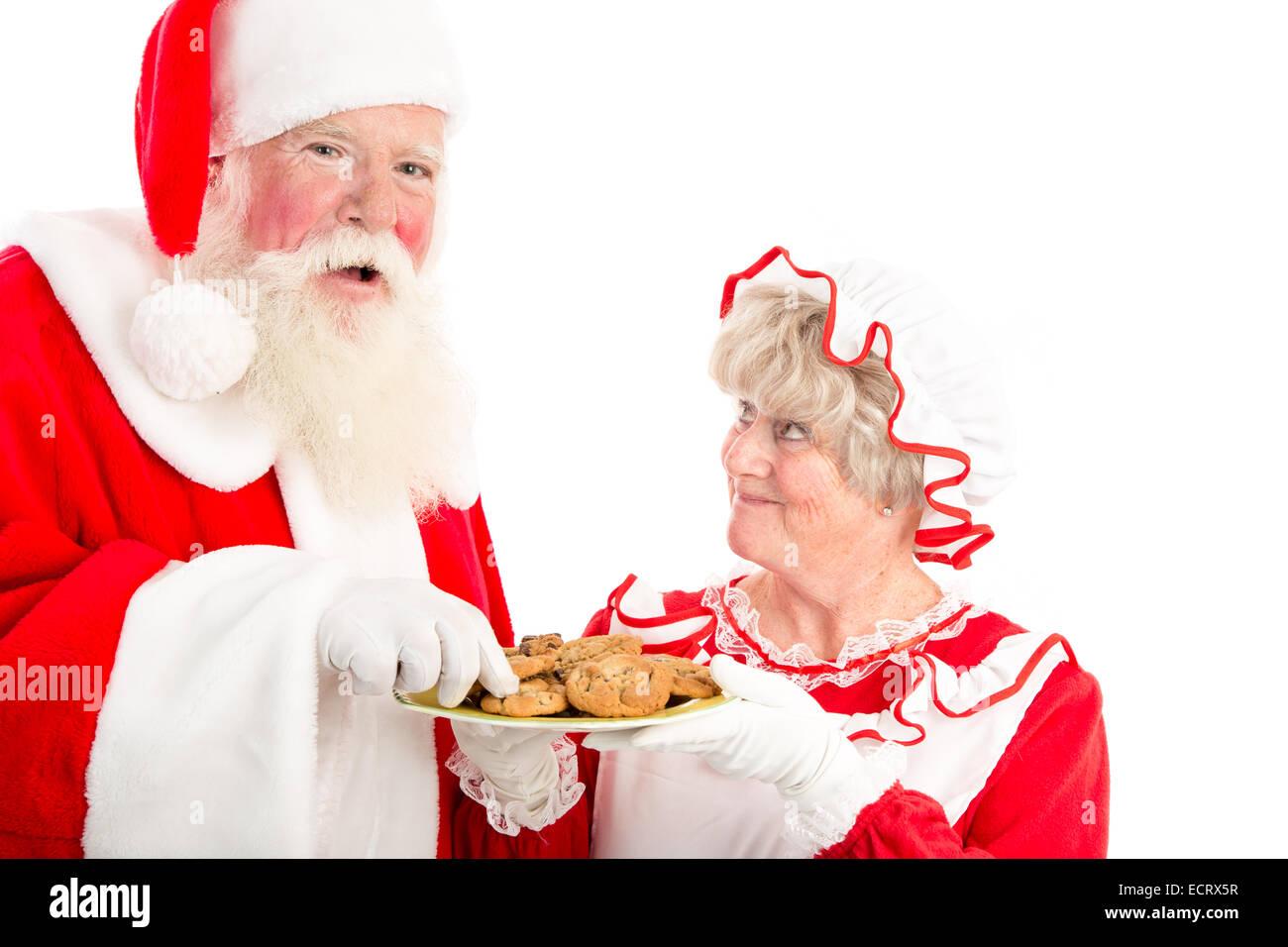 Un ridere Santa prende un cookie dalla piastra onorevole clausola offre lui. Immagini Stock