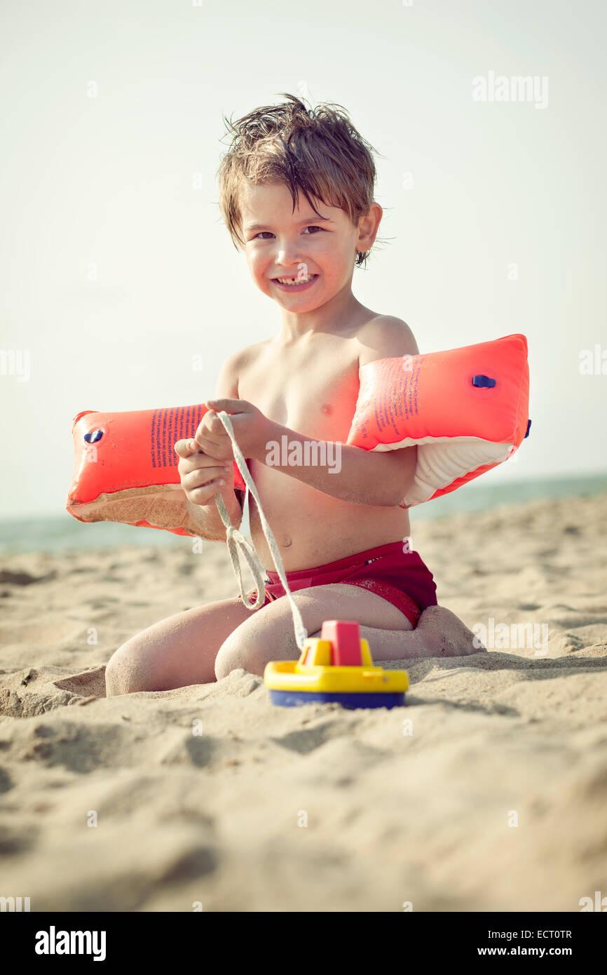 Sorridente piccolo ragazzo seduto sulla spiaggia con acqua le ali e la barca del giocattolo Immagini Stock