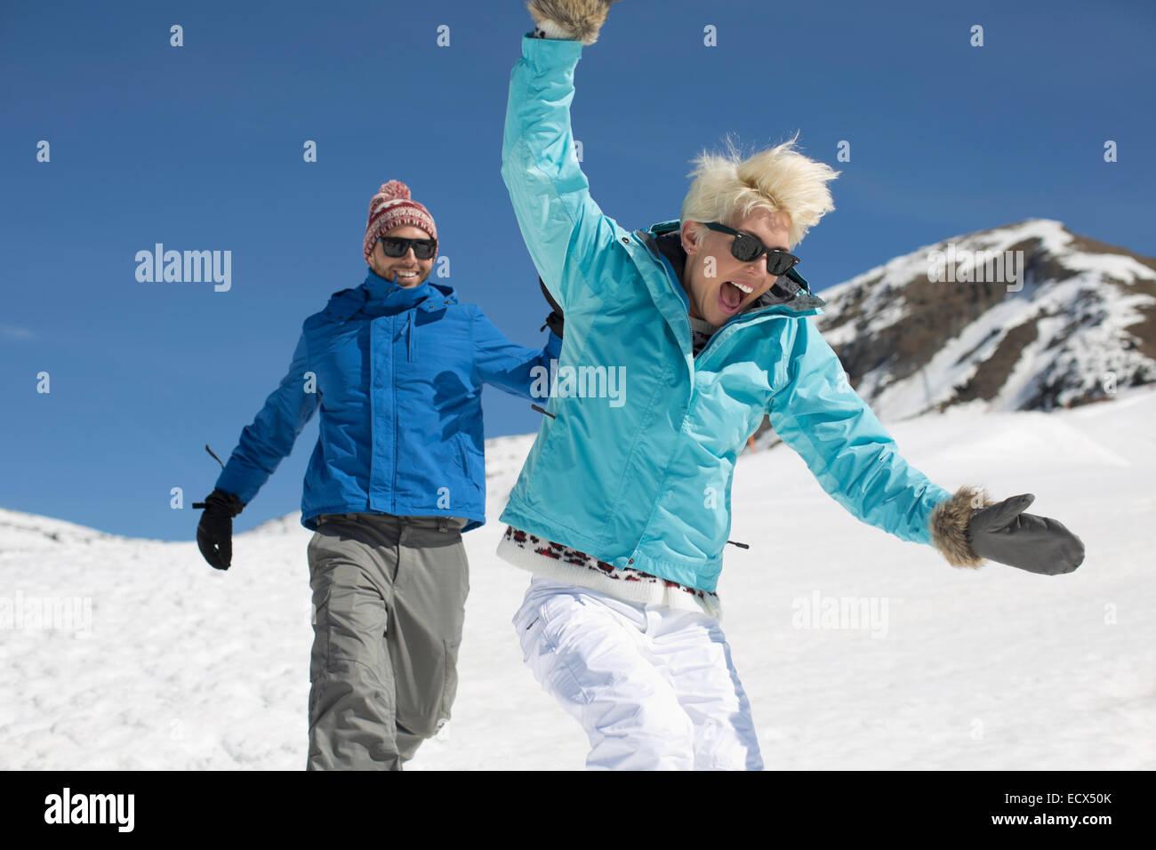 Coppia esuberante giocare nella neve Foto Stock