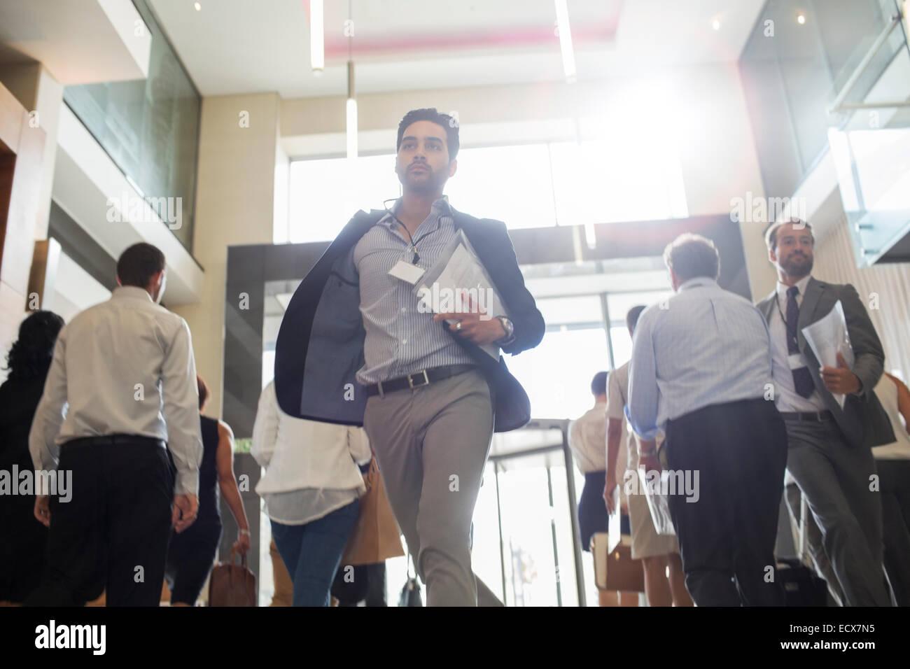 Uomini che tengono i documenti e in esecuzione nel corridoio di office Immagini Stock