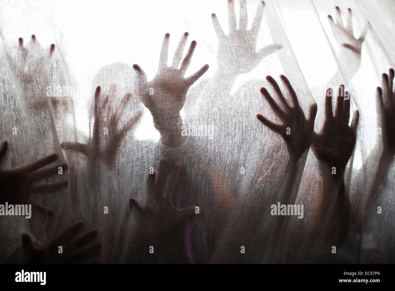 Silhouette di persone che allevano le mani dietro la tenda trasparente Immagini Stock
