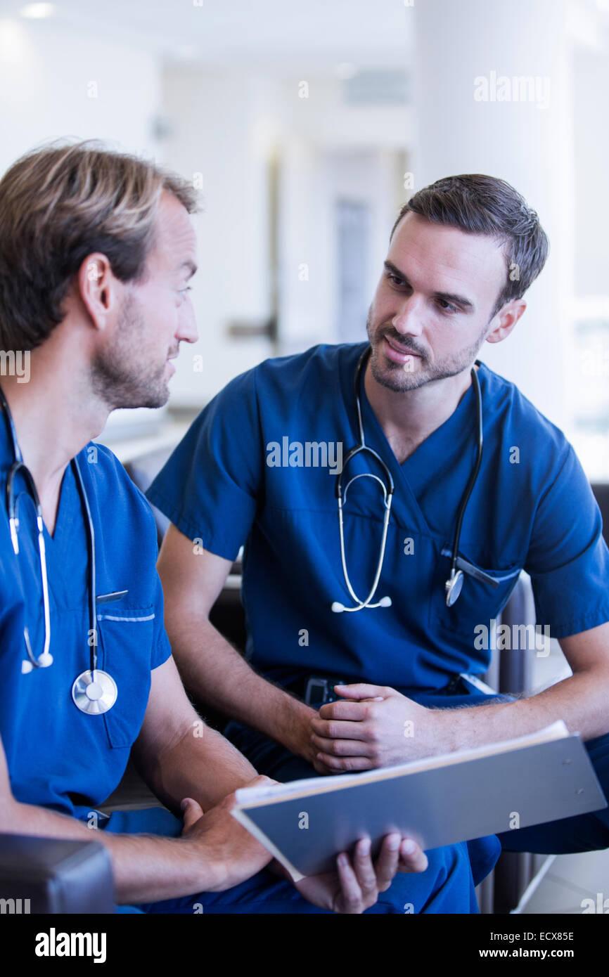 Due medici di sesso maschile con stetoscopi, indossando scrubs parlando in ospedale Immagini Stock