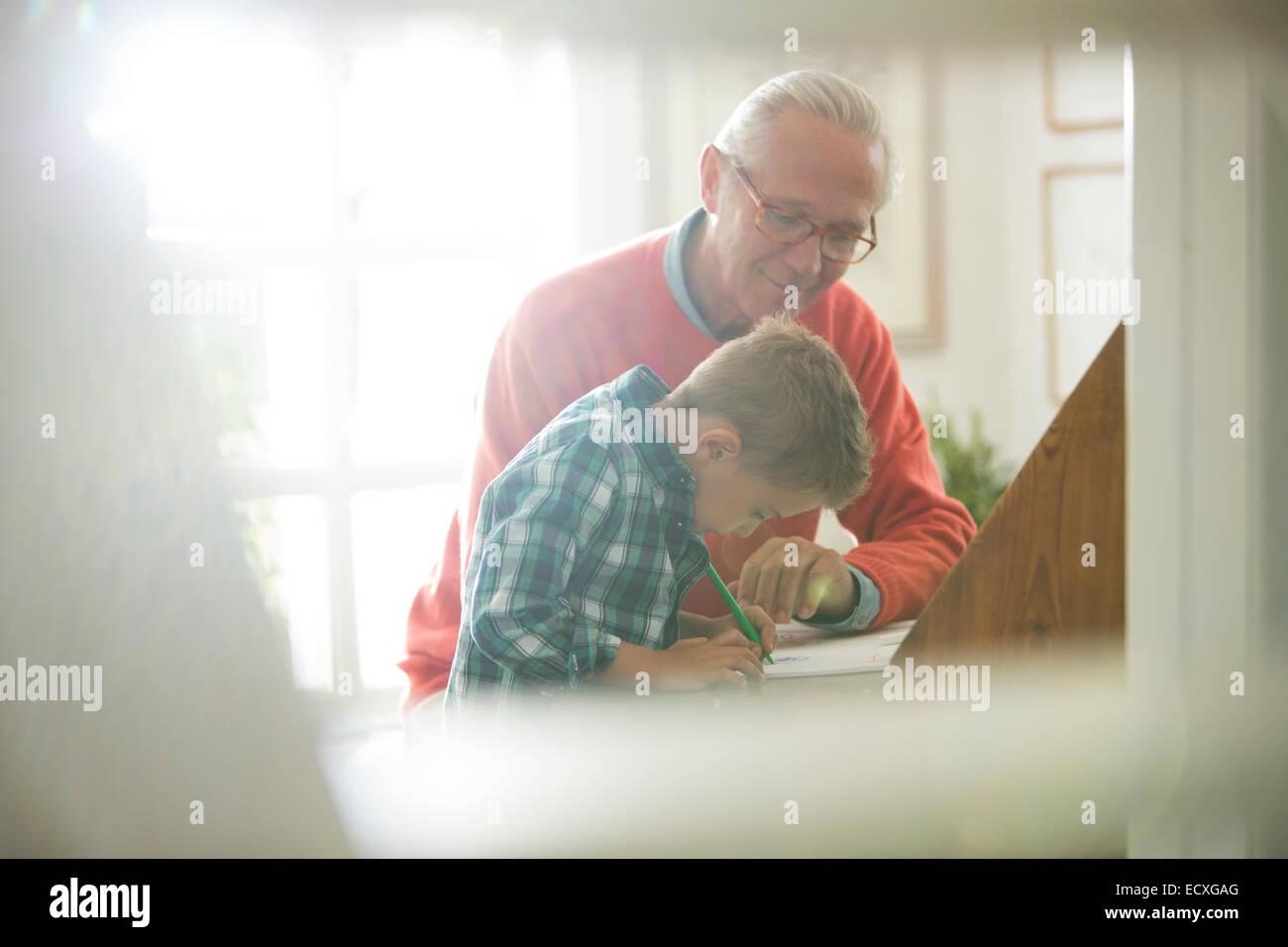 Nonno e nipote iscritto alla scrivania Immagini Stock
