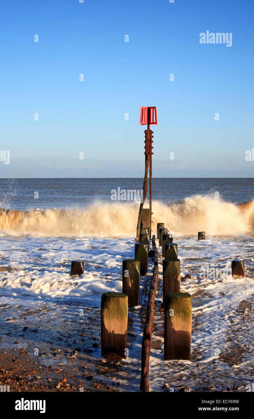 Un frangiflutti in legno e un marcatore di post in un mare moderato al carrello Gap, Norfolk, Inghilterra, Regno Immagini Stock