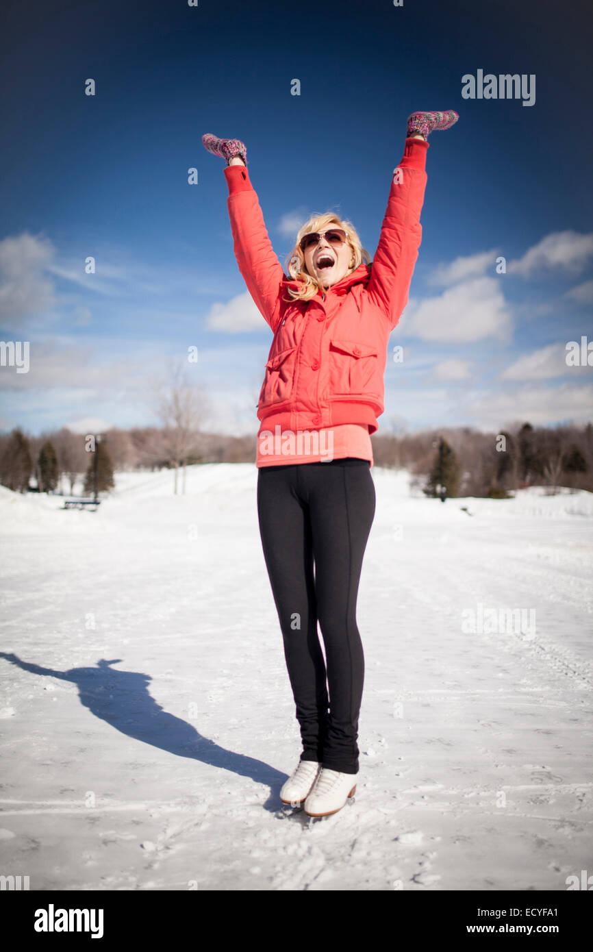 La donna caucasica su pattini da ghiaccio tifo sul lago ghiacciato Foto Stock