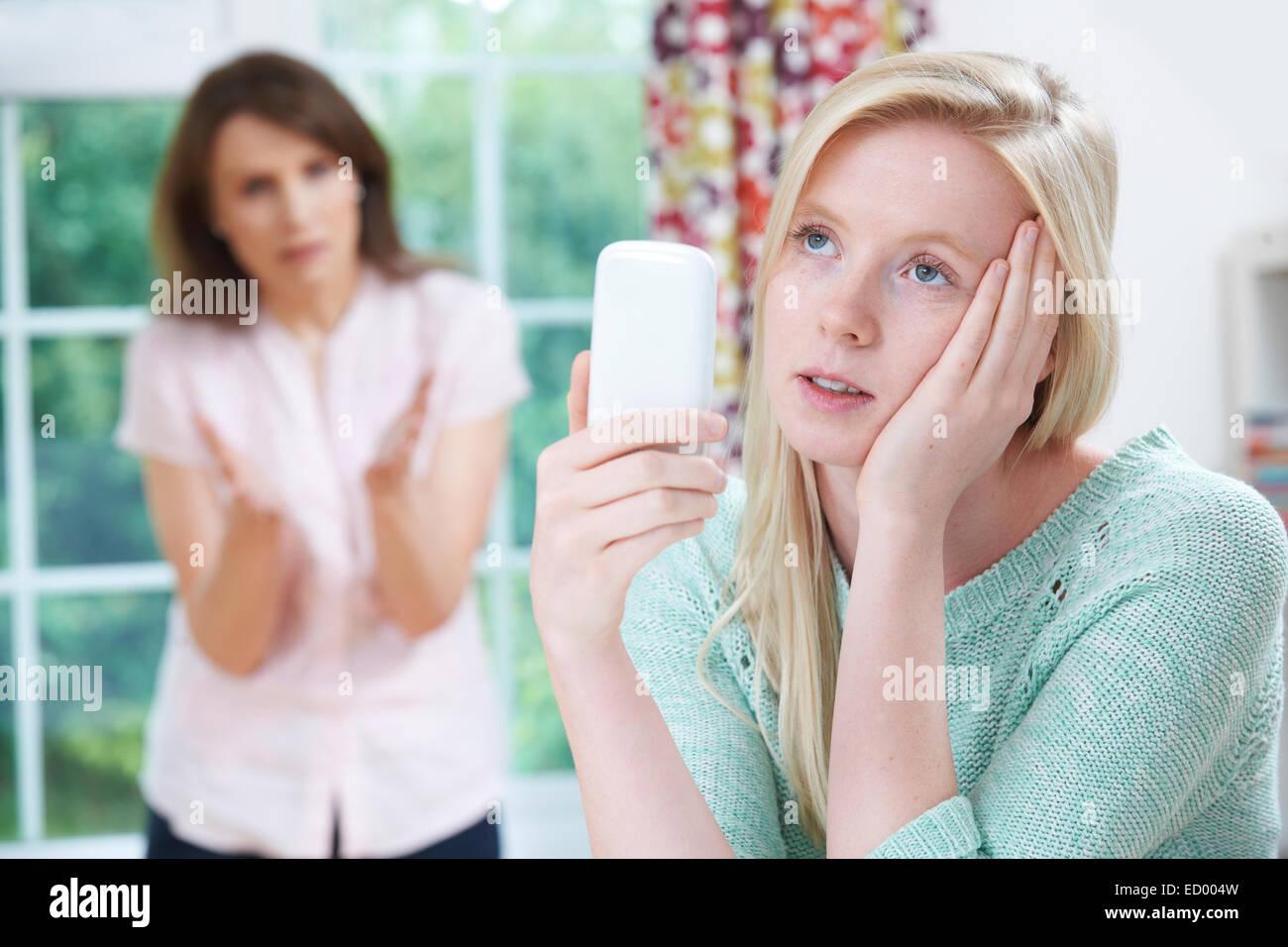 Madre sostenendo con la figlia adolescente su uso del telefono mobile Immagini Stock