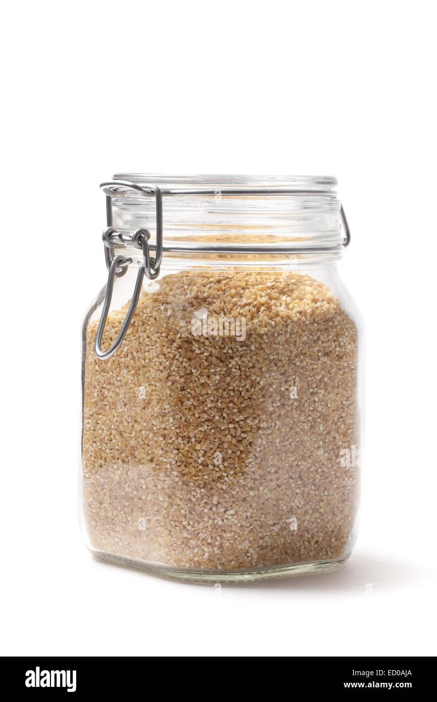 Immagine raw di semole in un vaso isolato su bianco. Immagini Stock