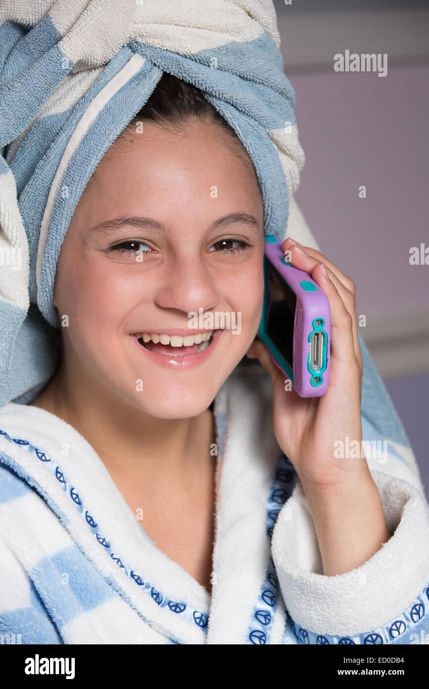 Ragazza seduta nella sua vestaglia parlando sul suo telefono cellulare Immagini Stock