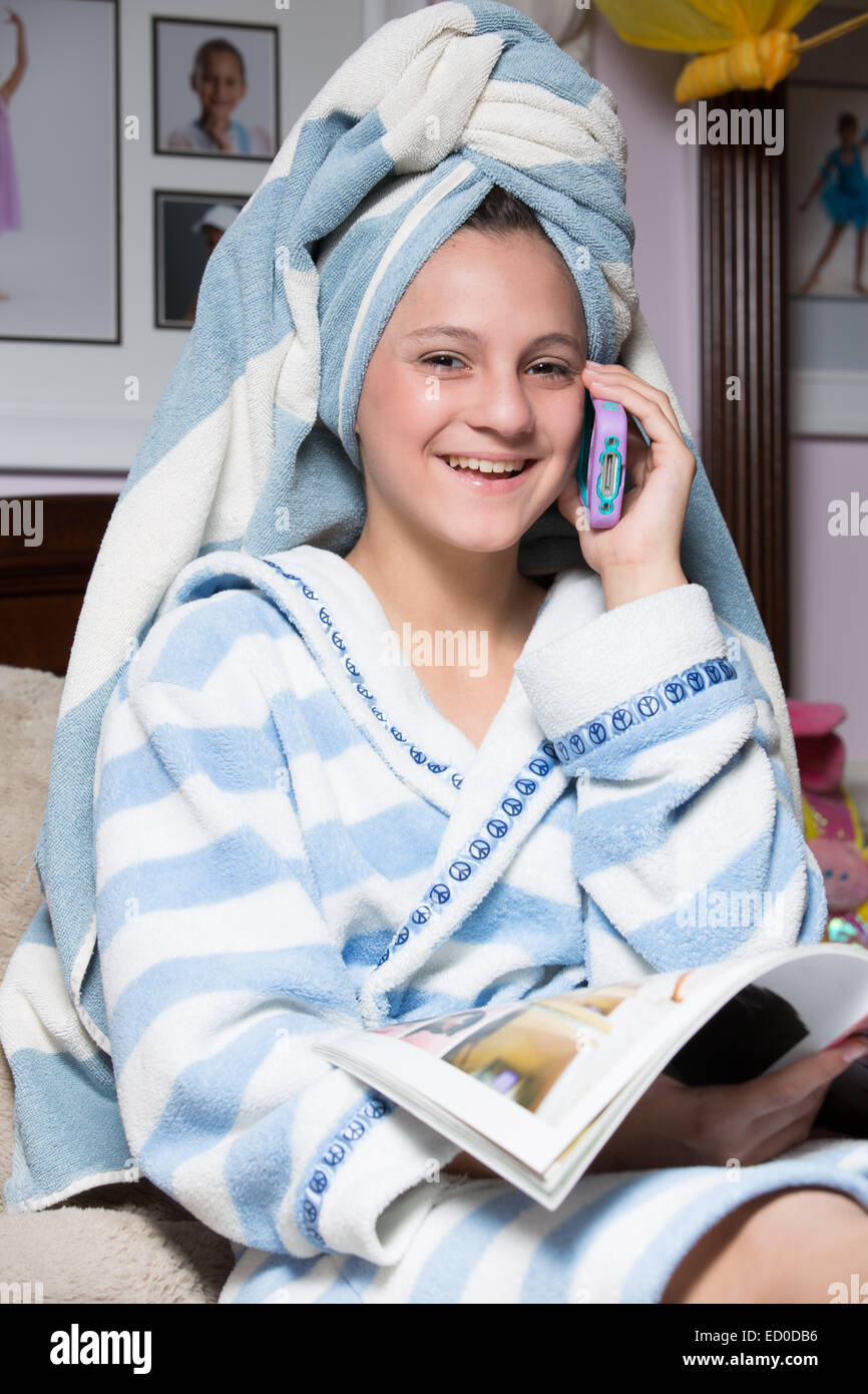 Ragazza in vestaglia parlando al telefono mentre la rivista di lettura Immagini Stock