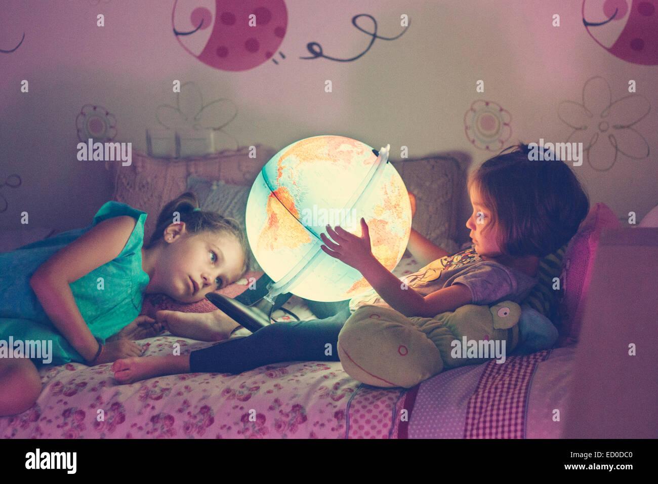 Due ragazze (2-3, 6-7) guardando accesa la lampada a forma di globo Immagini Stock