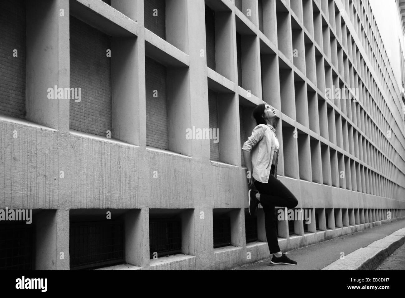 L'Italia, Milano, Donna appoggiata contro la parete Immagini Stock