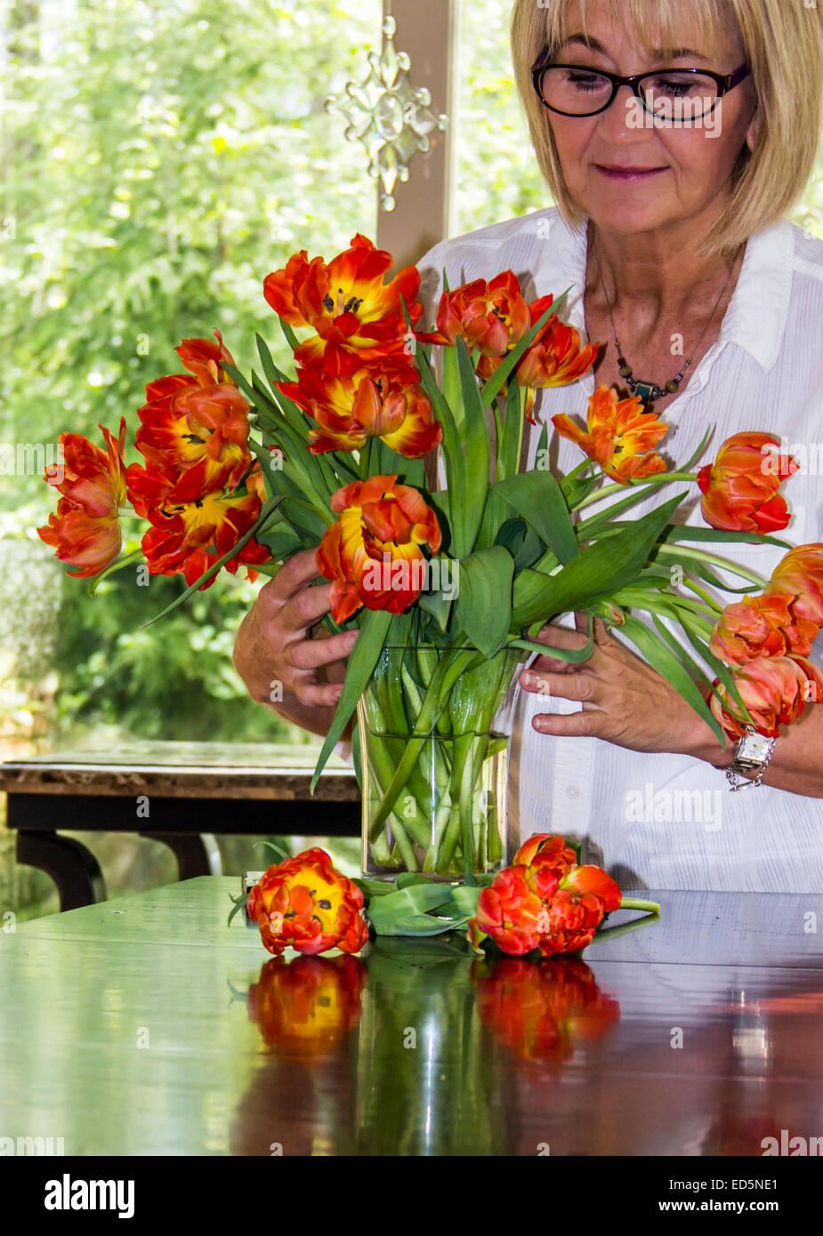 Adulta e matura donna caucasica disponendo un vaso di fiori o di tulipani in una luminosa casa con windows. Immagini Stock