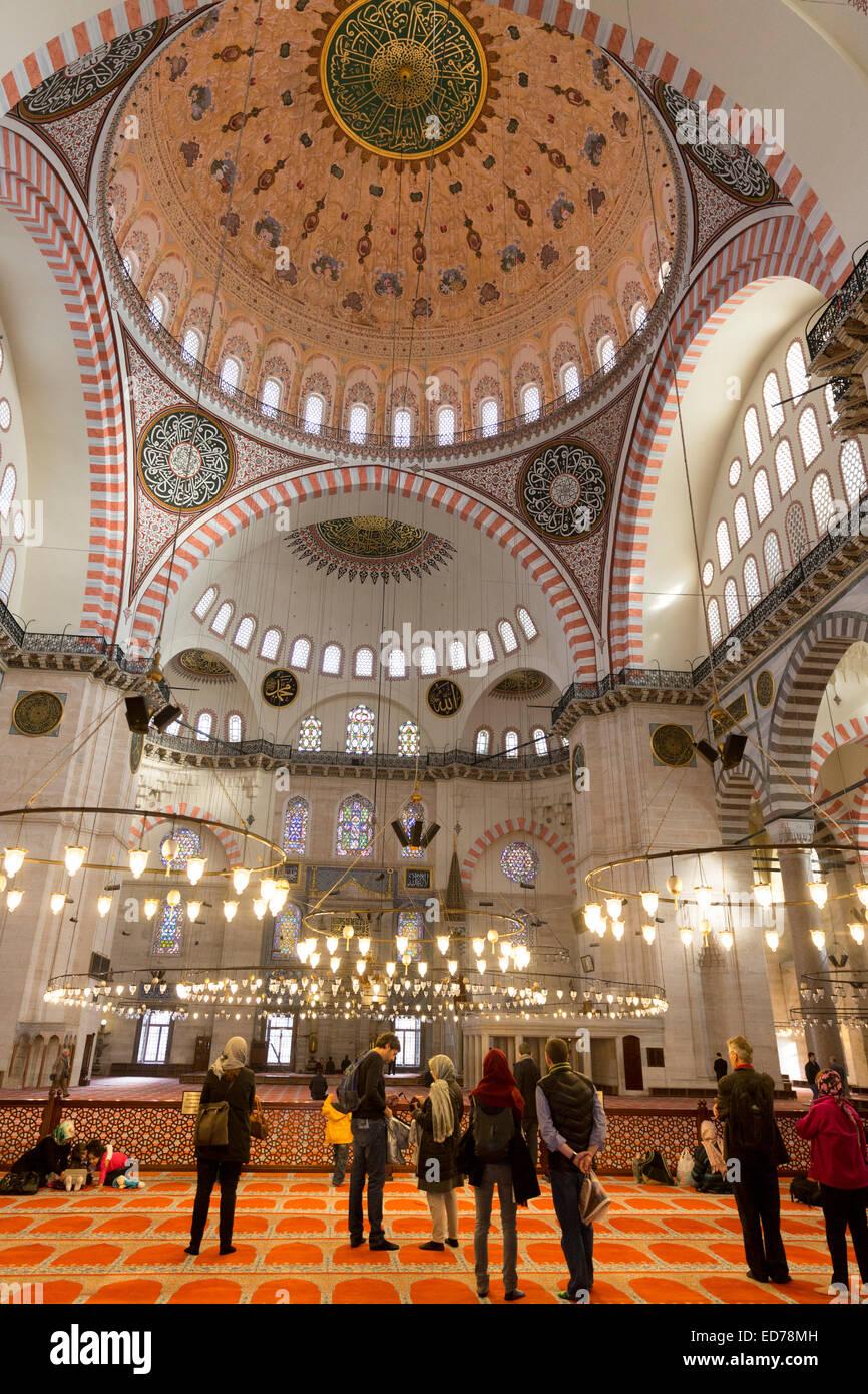 I turisti che indossa sciarpe in interno della Moschea Suleymaniye in Istanbul, Repubblica di Turchia Immagini Stock