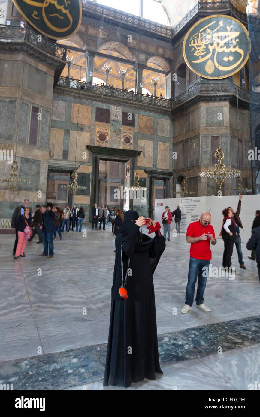Donna musulmana a Hagia Sophia, Ayasofya Muzesi museo della moschea di indossare niqab utilizza lo smartphone scattare Foto Stock