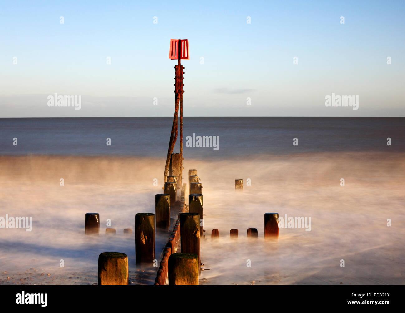 Una immagine creativa di una struttura di frangionde con marcatore post in un mare moderato al carrello Gap, Norfolk, Immagini Stock
