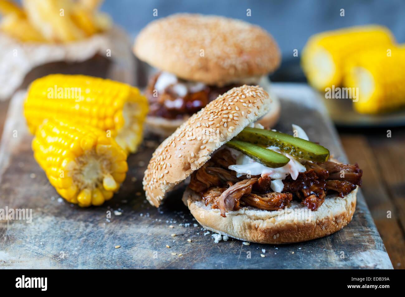 Burger con estratto di carne di maiale, granturco dolce e trucioli Immagini Stock