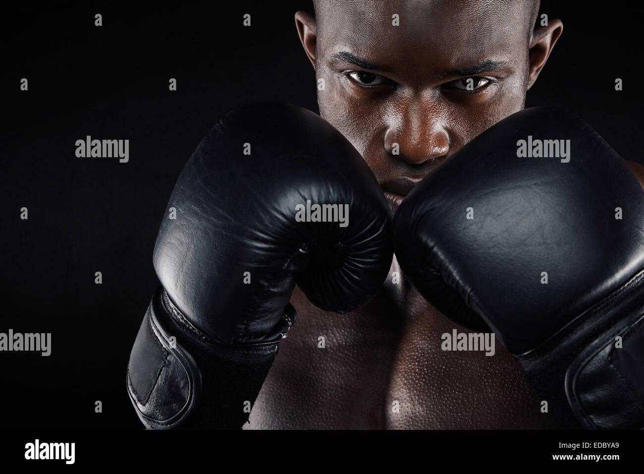 Ritratto di un giovane maschio boxer in un atteggiamento di combattimento su sfondo nero. Giovane uomo facendo esercizio Immagini Stock