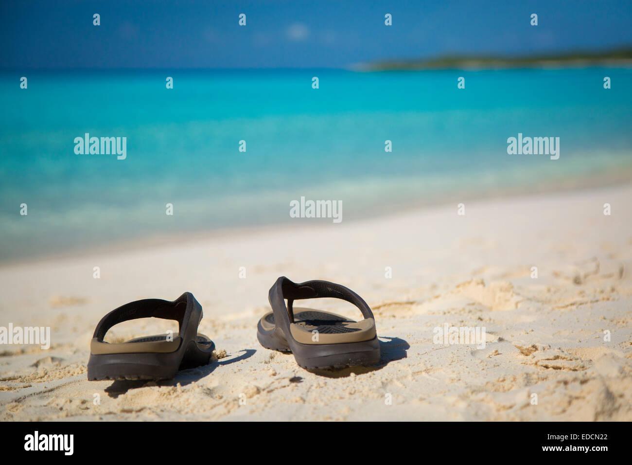 Il flip flop su di una spiaggia di sabbia con 'turqoise' acqua al di là, halfmoon Cay, Bahamas Immagini Stock
