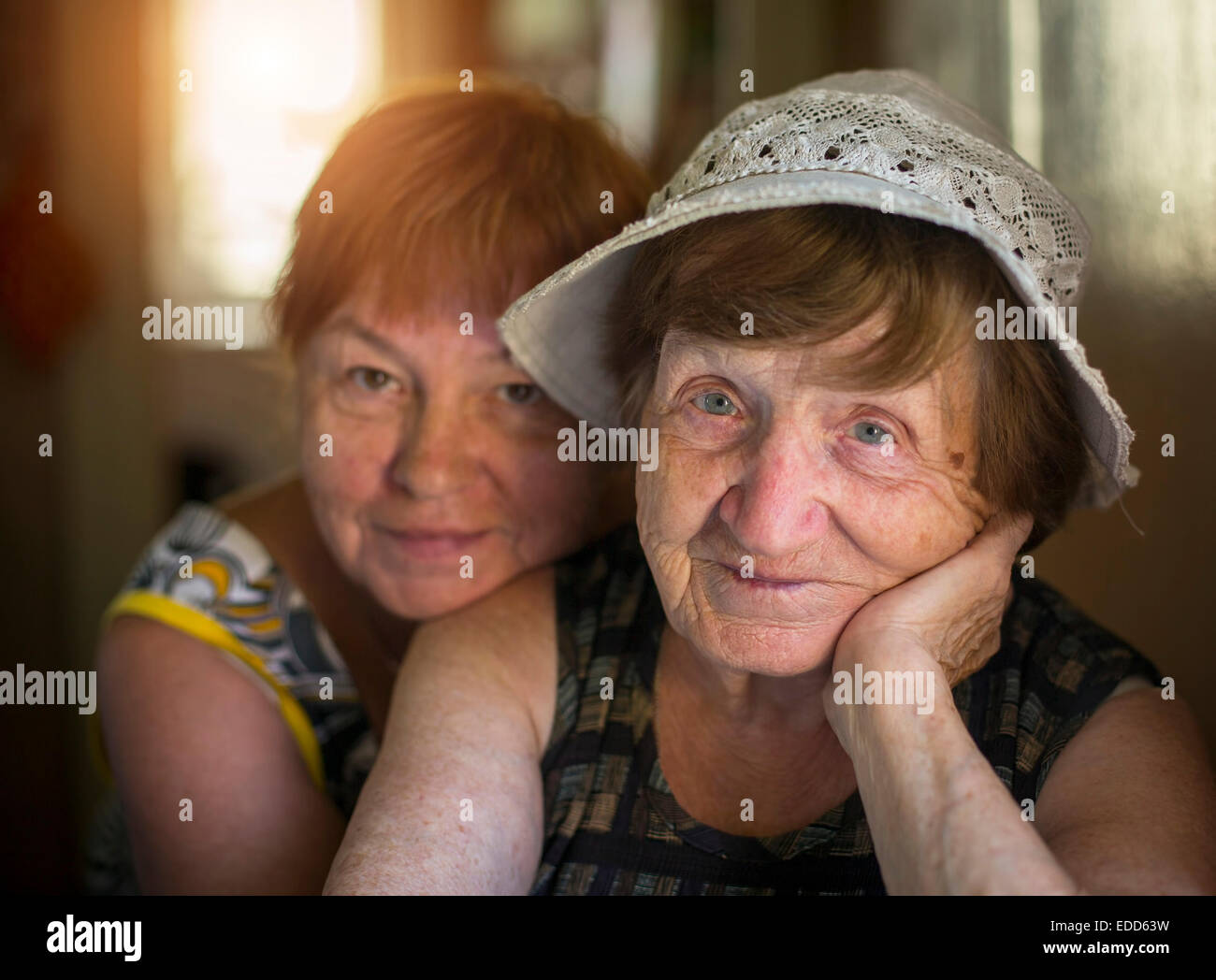 Ritratto di donna anziana e abbracciando la figlia in background, in casa. Immagini Stock