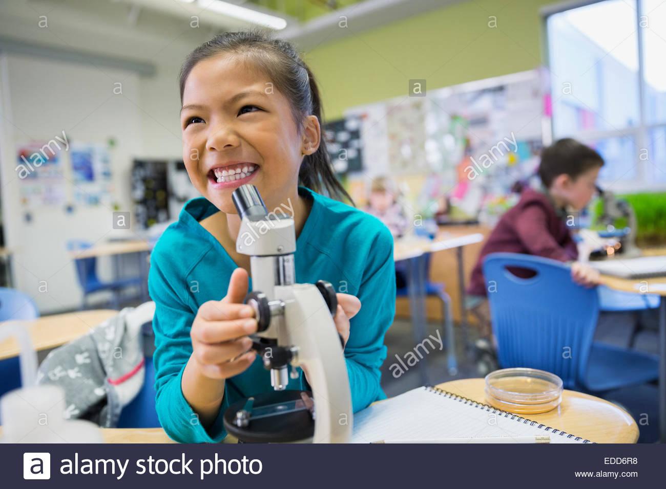 Entusiasta studente elementare mediante microscopio in laboratorio Immagini Stock