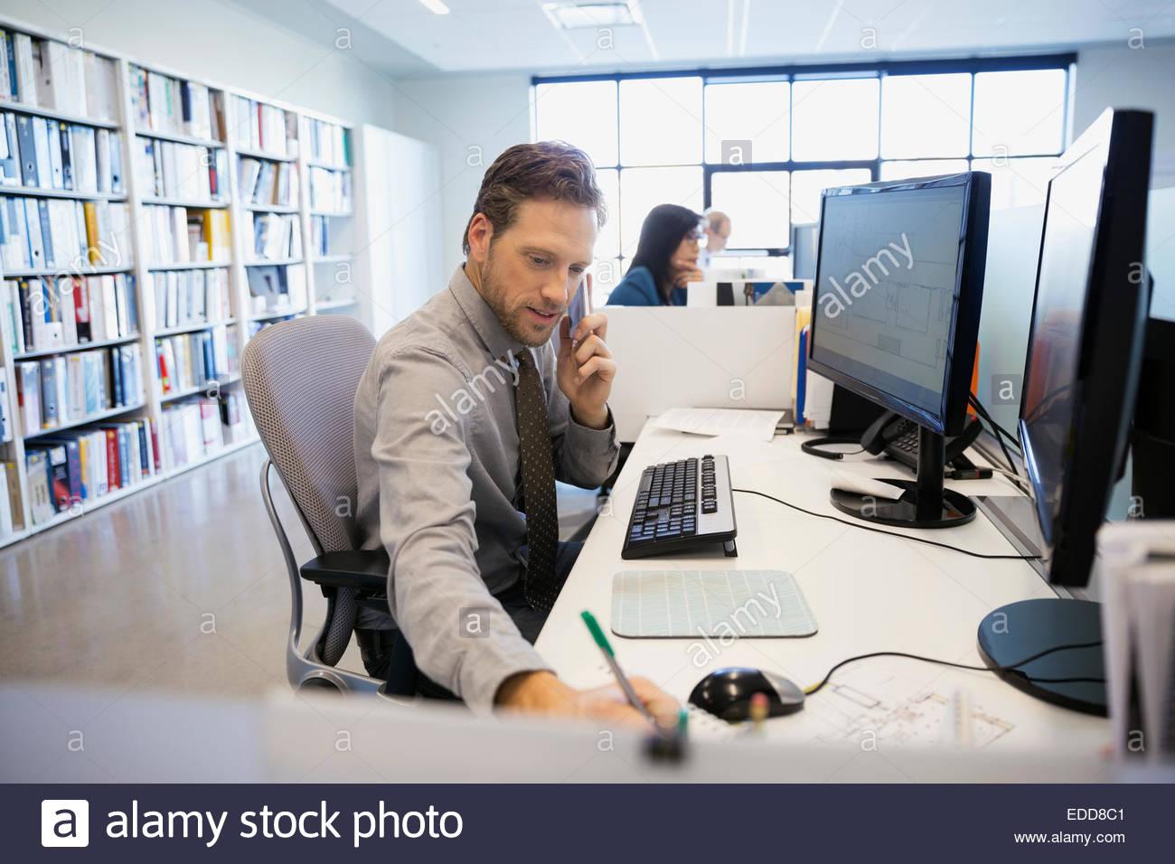 Imprenditore parlando al cellulare a scrivania da ufficio Immagini Stock