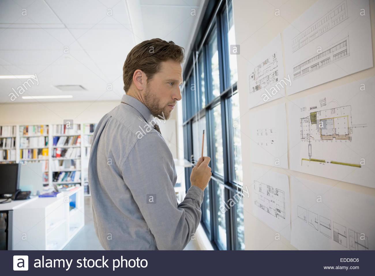 Architetto esaminando i piani sulla parete Immagini Stock