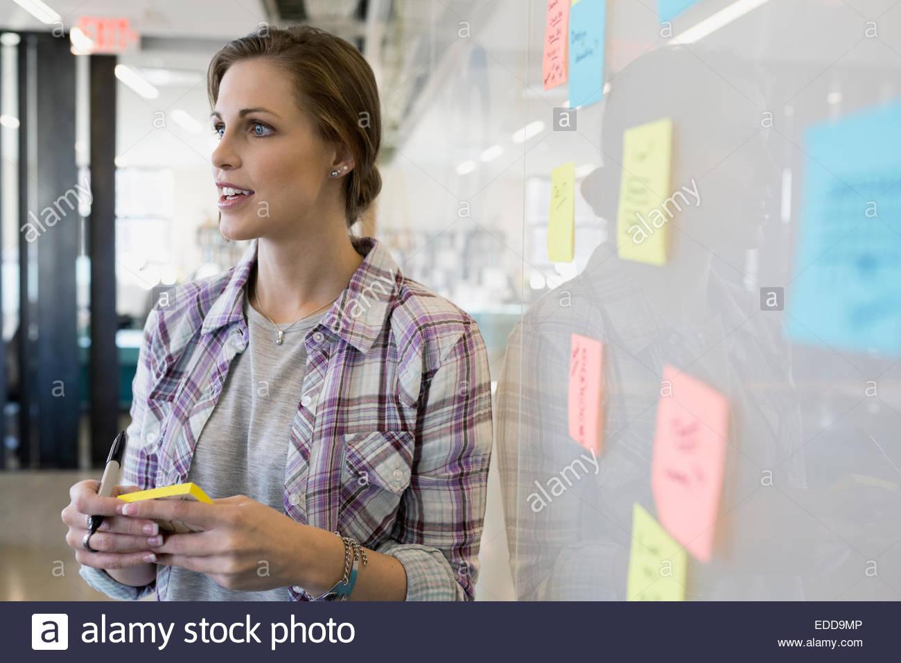 Imprenditrice la scrittura di note adesive su whiteboard Immagini Stock