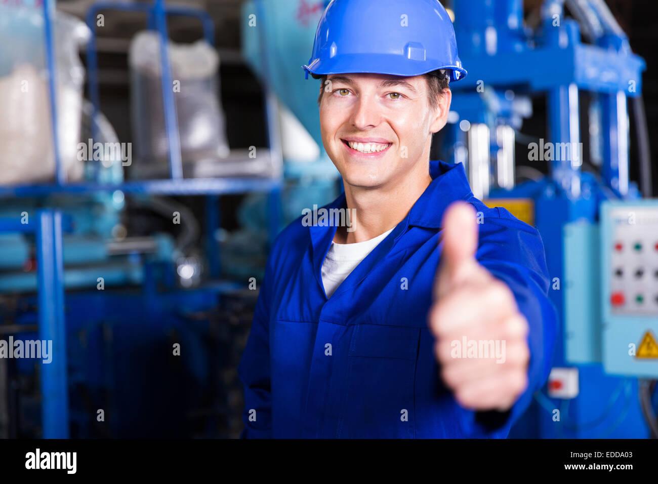 Allegro lavoratore pollice in su in fabbrica Immagini Stock