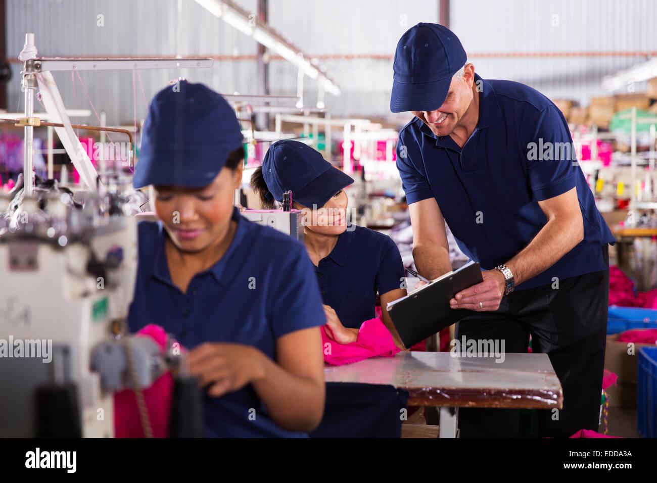 Abbigliamento sorridente factory foreman spiegando il lavoro ai giovani macchinista Immagini Stock
