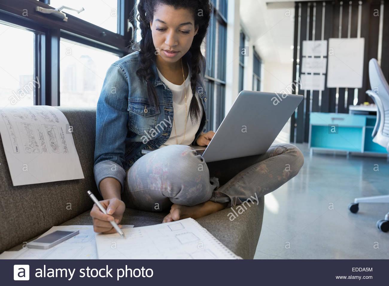 Designer che lavora al computer portatile sul divano in office Immagini Stock