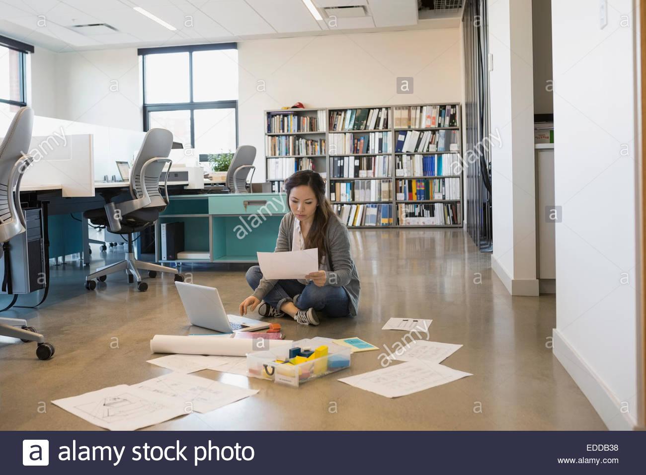 Designer che lavora al computer portatile sul pavimento in ufficio Immagini Stock