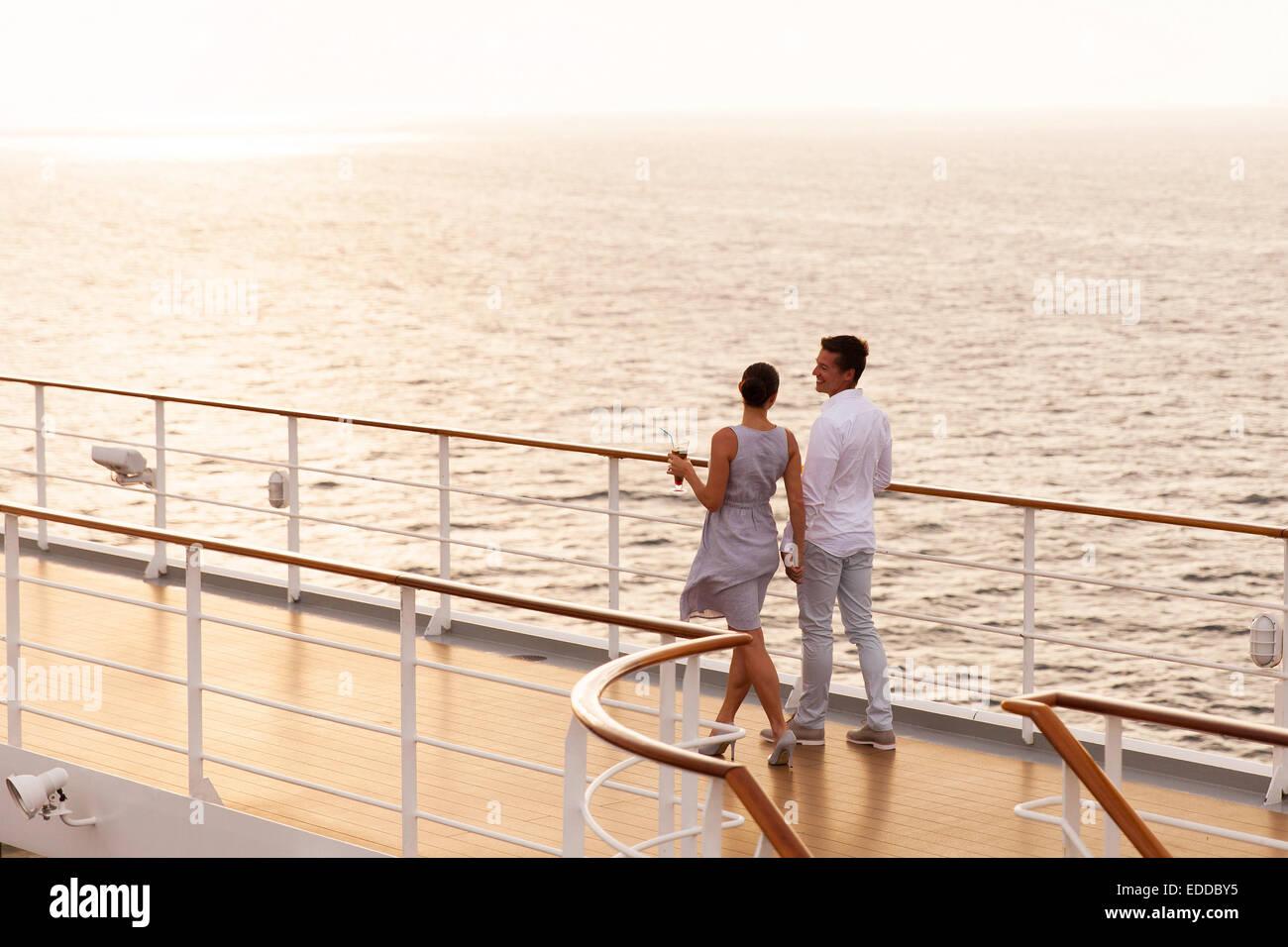Carino coppia camminando su una nave da crociera il ponte al tramonto Immagini Stock