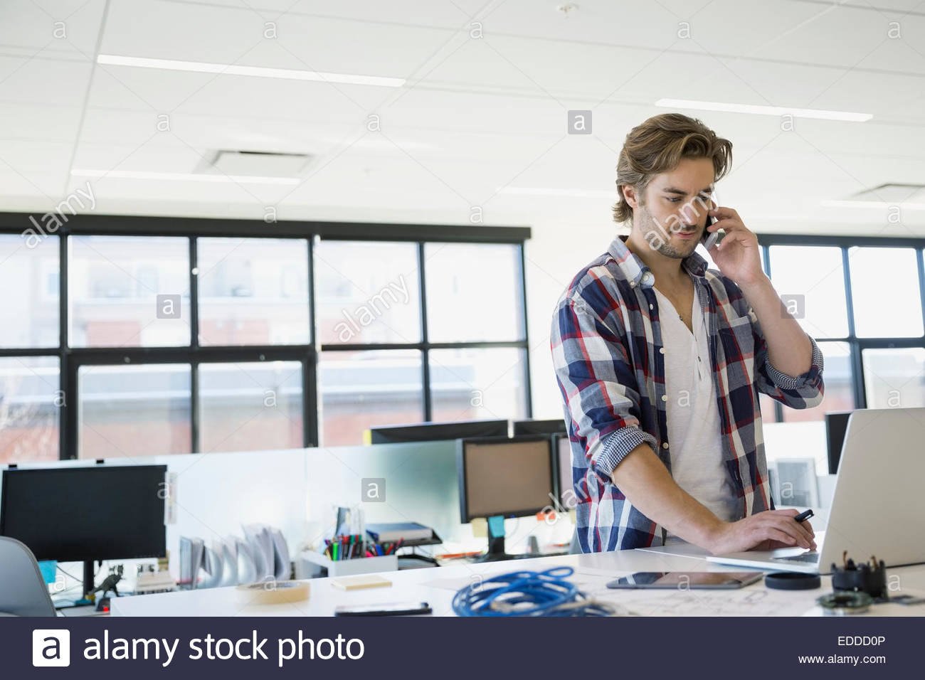 Imprenditore a laptop parlando al cellulare Immagini Stock