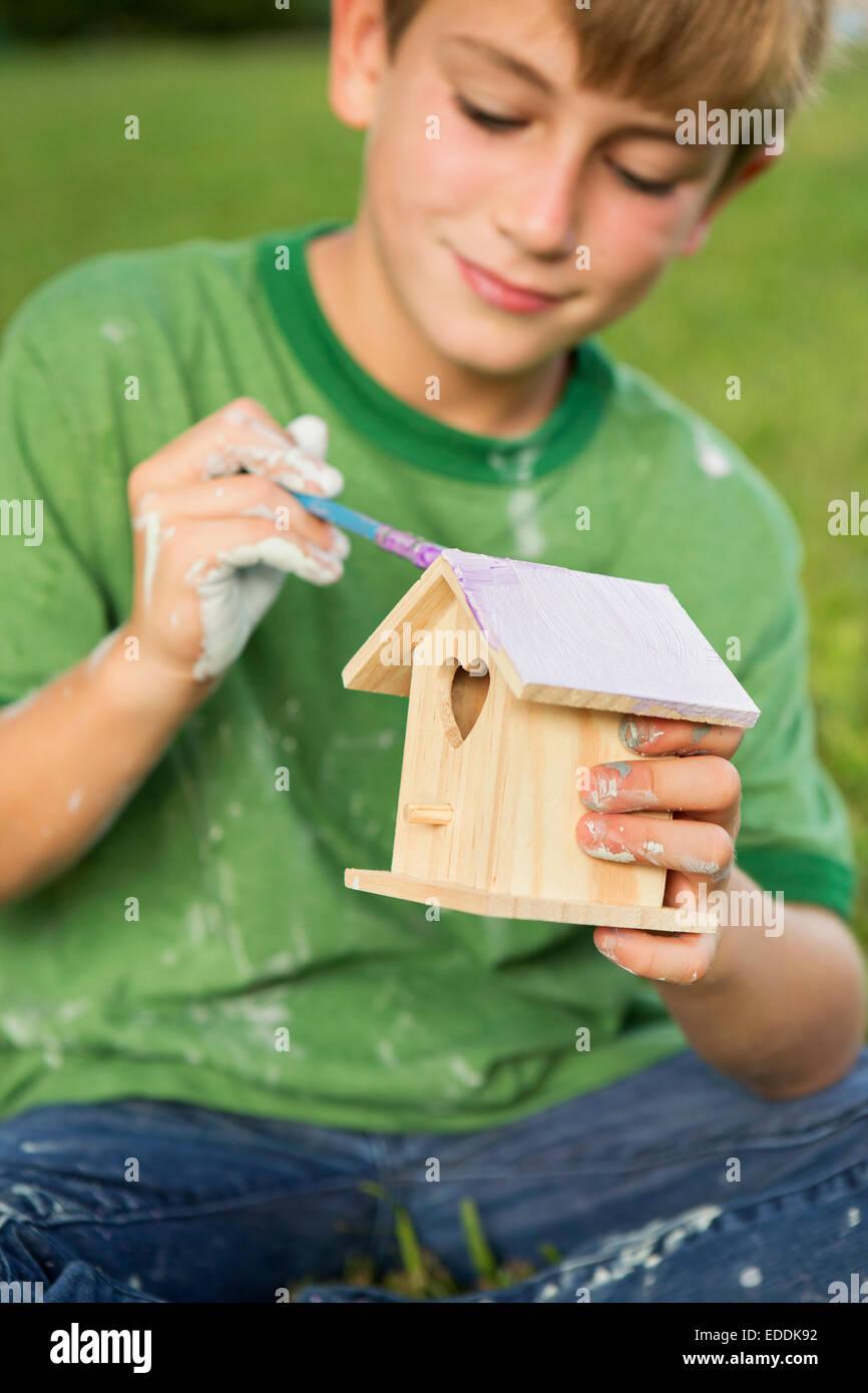 Un ragazzo in un giardino, la pittura di un uccello house. Immagini Stock