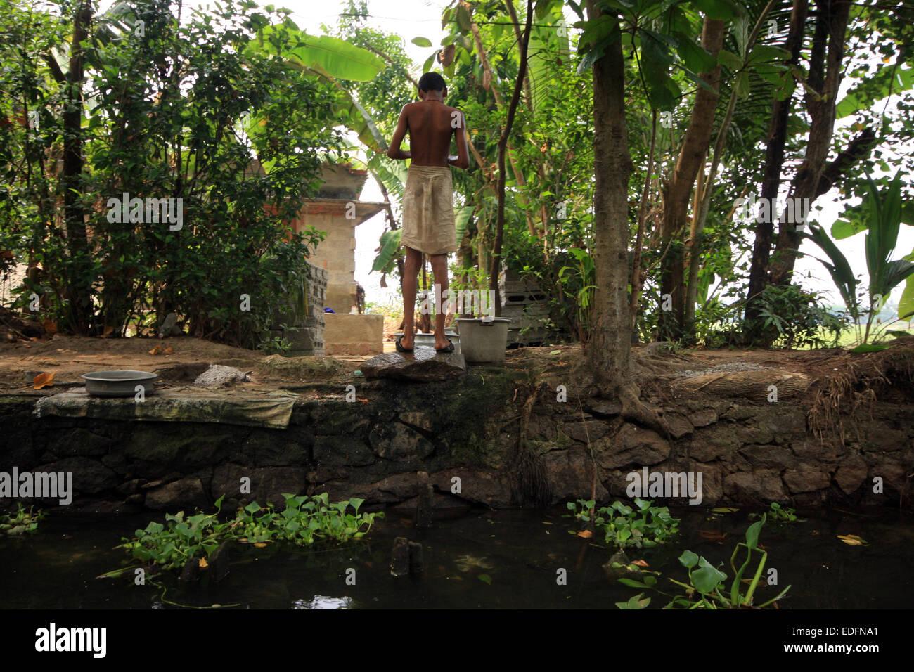 Lavaggio del ragazzo accanto al fiume nelle backwaters vicino Alleppey Immagini Stock