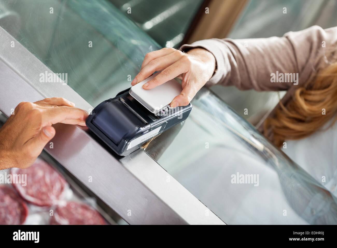 Il cliente effettuando il pagamento tramite smartphone nella macelleria Immagini Stock