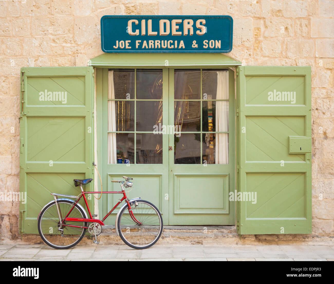 Retrò bicicletta rosso al di fuori di porte verdi della tradizionale doratori shop Mdina Malta EU Europe Immagini Stock