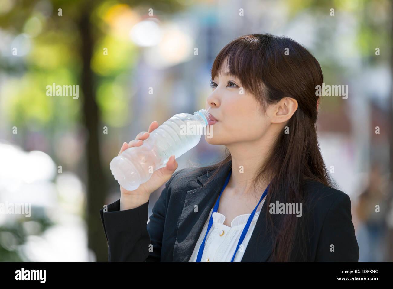 Imprenditrice di bere acqua in bottiglia Immagini Stock
