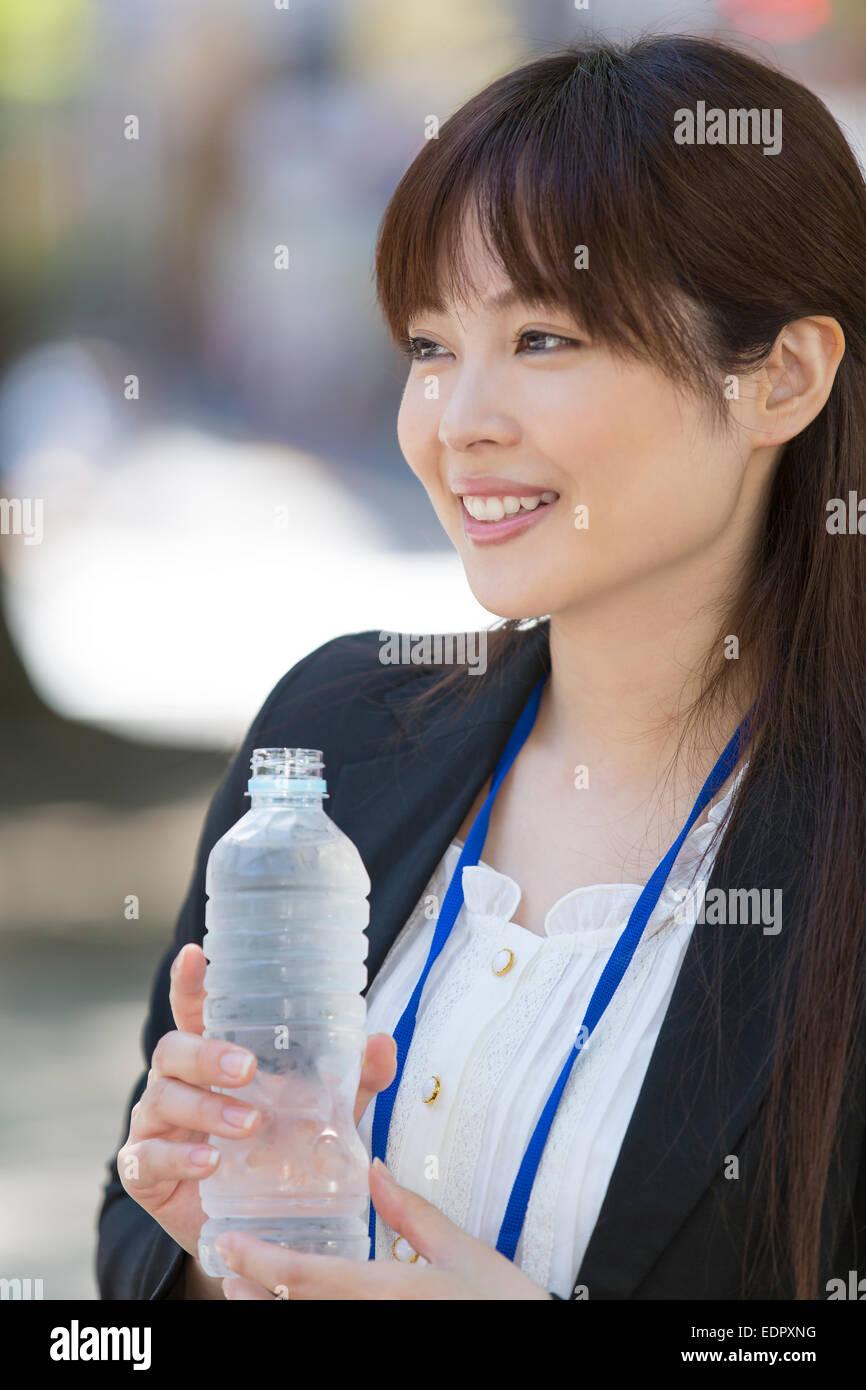 Sorridente imprenditrice di contenimento acqua in bottiglia Immagini Stock