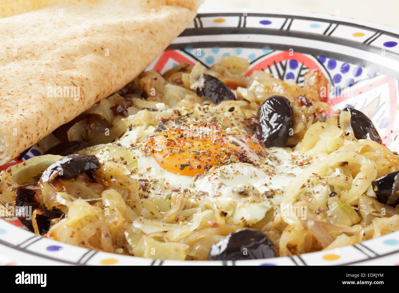 Piatto marocchino di cipolle, aglio, peperoncino, olive nere, l'uovo e Za'atar Immagini Stock