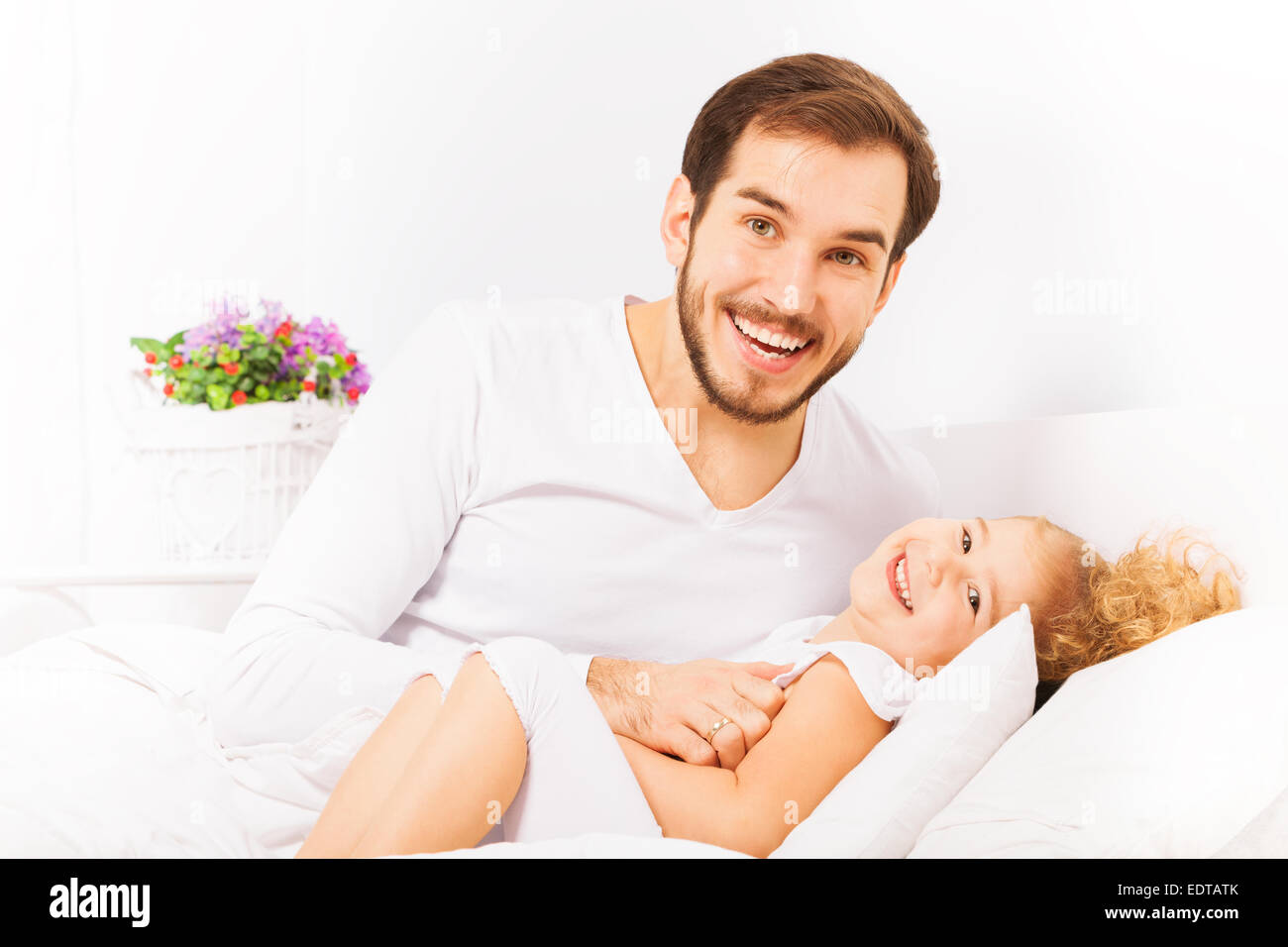 Padre abbracci carino figlia e la posa sul letto Foto Stock