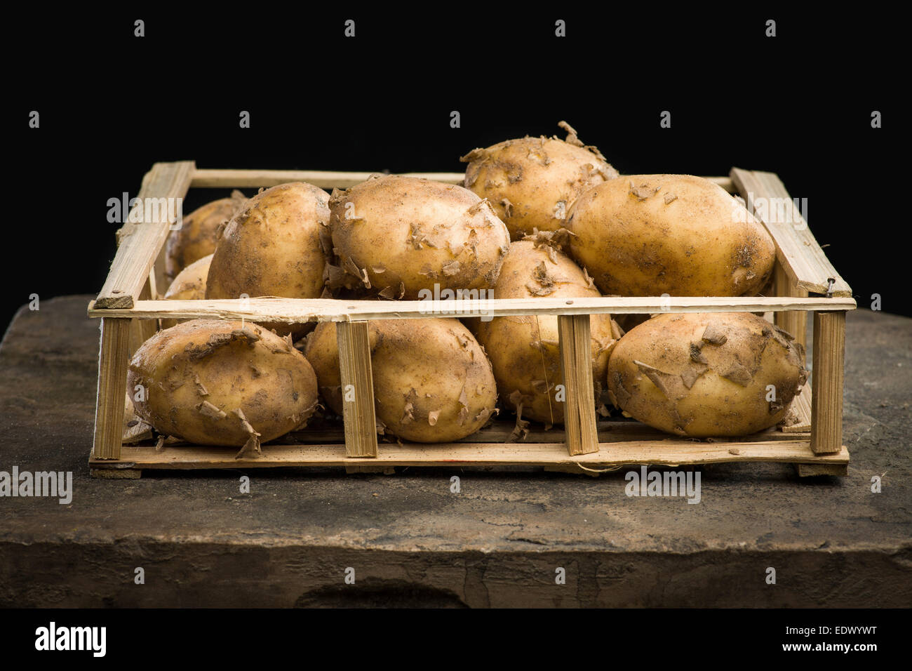 Young Mature le patate in una cassa di legno su sfondo scuro Immagini Stock