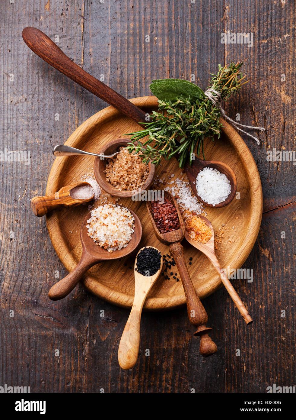 Diversi tipi di alimenti sale grosso in cucchiai di legno su sfondo scuro Immagini Stock