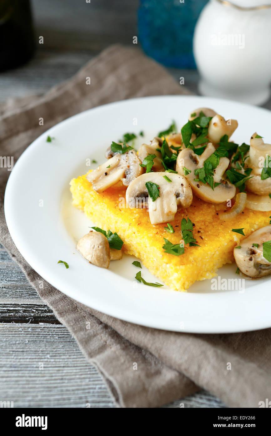 Gustosa la polenta con i funghi in una piastra bianca, cibo close up Foto Stock